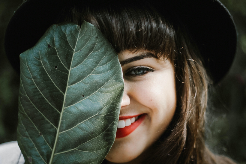Health is easy: Woman smiling with leaf.