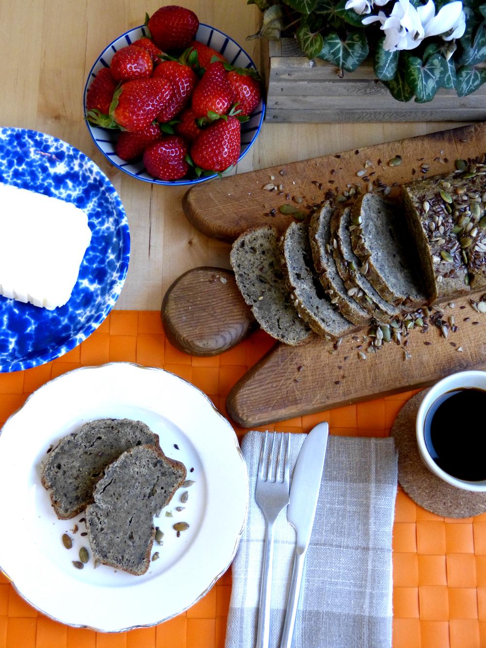 Three Seed Paleo Bread, sliced on a wooden bread board.