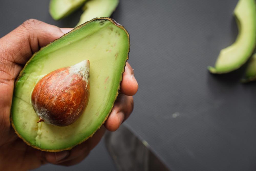 Hand holding avocado.