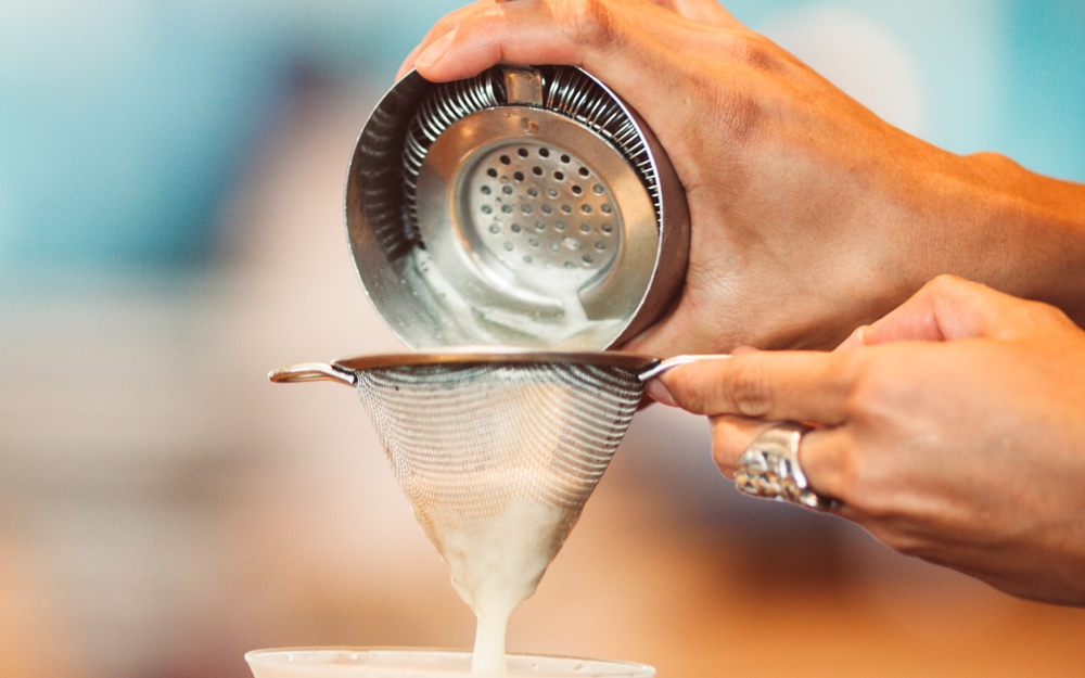 Hand pouring substance through a sieve.