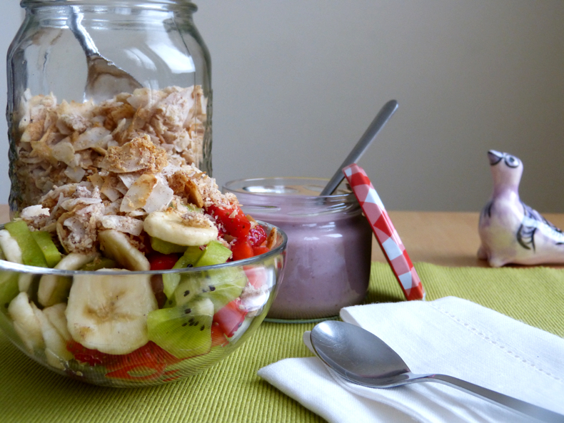Real Simple Grain Free Paleo Granola, in a jar, with a bowl of fruit salad.