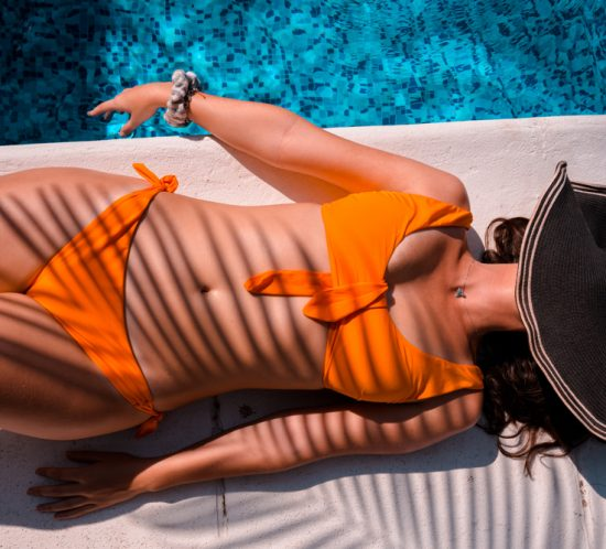 Woman sunbathing next to a pool: Avoid Vitamin D deficiency.