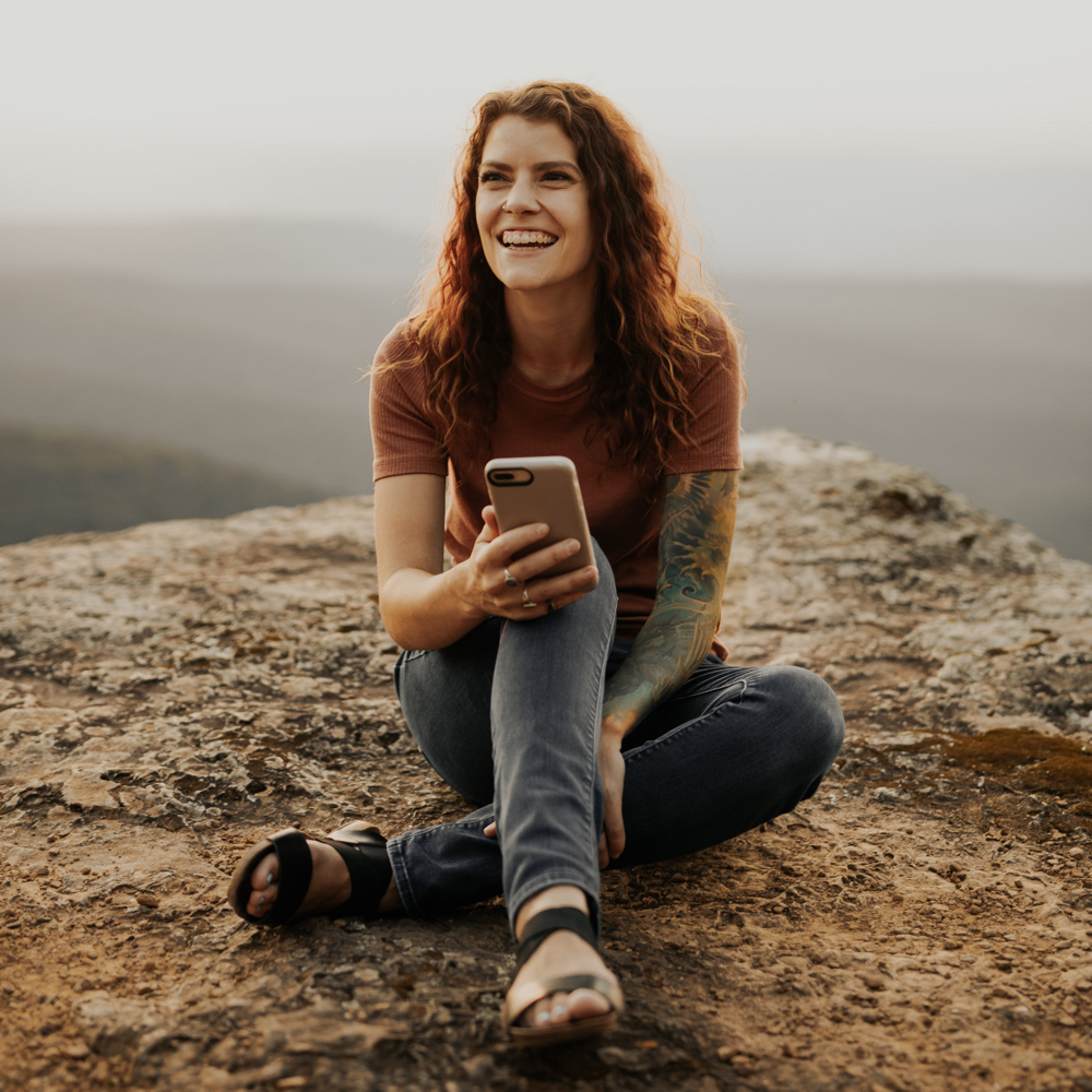 Woman in nature with smartphone.
